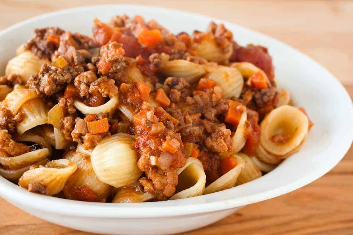 Meaty Italian Bolognese sauce doesn't have to take all day to make; grab a second pan and you'll have it done in 2 hours. #bolognese #italian