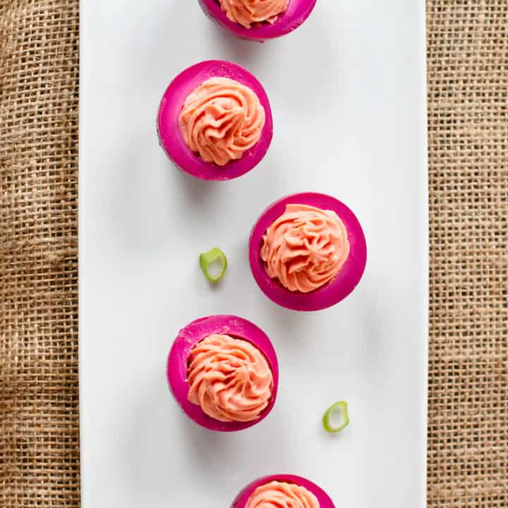 Beet-pickled eggs have a bright fuchsia exterior and a creamy sweetness from beet brine. Eat this Pennsylvania Dutch specialty plain or as deviled eggs. #beetpickledeggs #deviledeggs