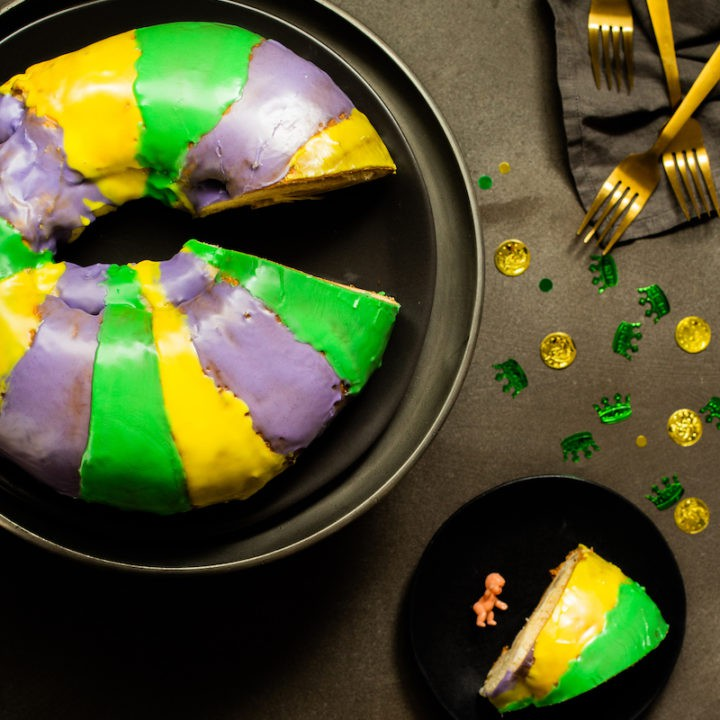 Mardi Gras king cake, the traditional tricolored dessert hailing from New Orleans, is a good-luck charm for the New Year. Make your own homemade cake with cream cheese filling. #mardigras #kingcake
