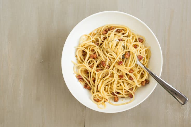 Spaghetti carbonara, with eggs, black pepper, pancetta, and Parmesan cheese, is one of the easiest and most satisfying pasta dishes around. No cream! #spaghetticarbonara #pastacarbonara #easyitalian