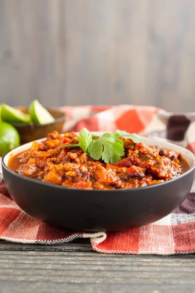 Black bean chili with cilantro brings a summery dimension to the fall/winter comfort staple, but can be made without the herb for cilantro haters.