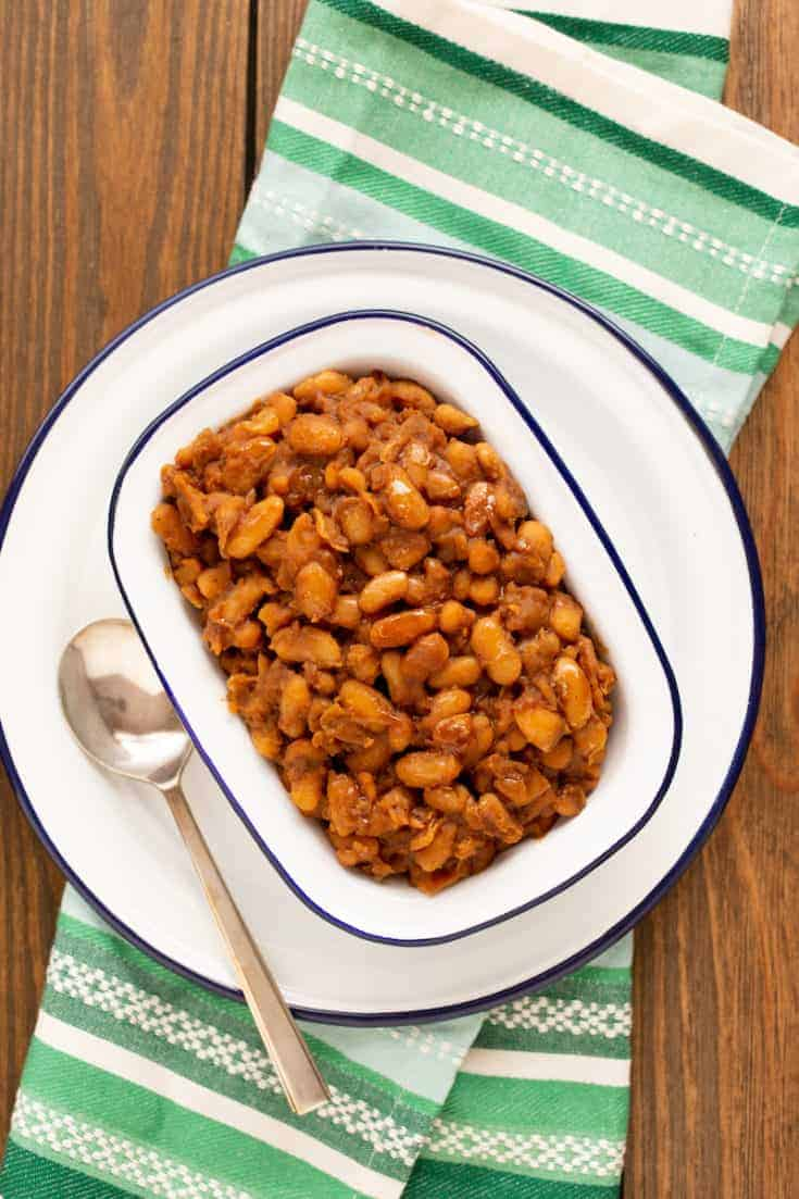 Baked beans showcase the perfect blend of tangy and sweet flavors in this recipe for the classic American dish. And yes, they're vegetarian. #bakedbeans #bbq #vegetarian