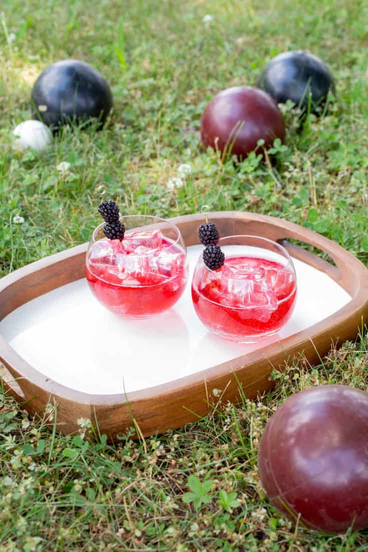The colors of black and red in this blackberry Campari cocktail honor the Italian game of bocce. And you can drink it while playing! #campari #cocktail #summercocktail