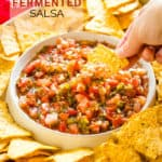 dipping a chip into fermented salsa