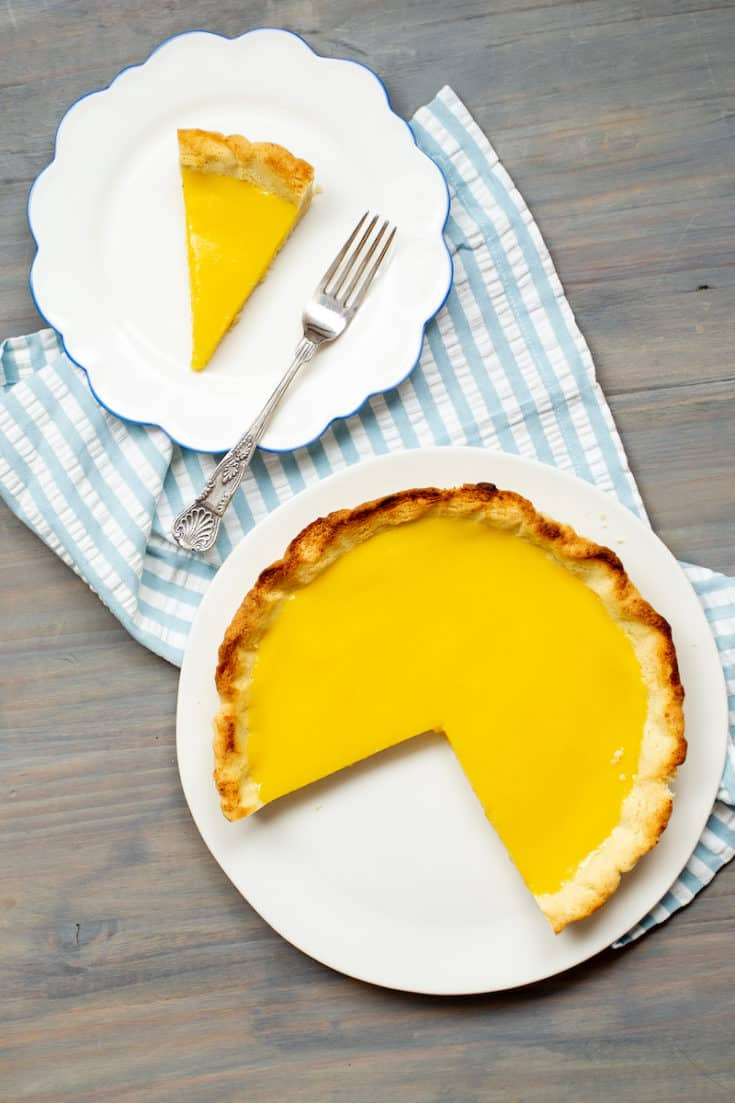 This rich and puckery lemon olive oil tart is dairy-free, but you'd never realize it from the smooth, thick lemon curd and sweet coconut-enhanced crust. #lemontart #dairyfree