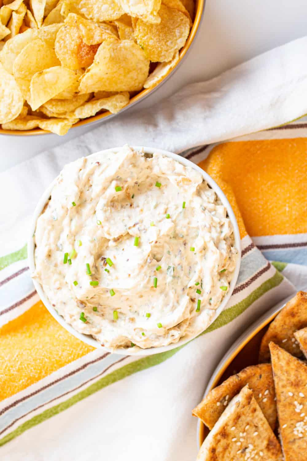 french onion dip with potato chips and pita chips