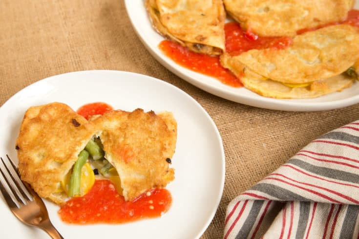 Peneques—puffy battered stuffed tortillas—stuffed with vegetables are a great seasonal meal. Try this recipe with fresh ranchera sauce. #peneques #mexican #vegetarian
