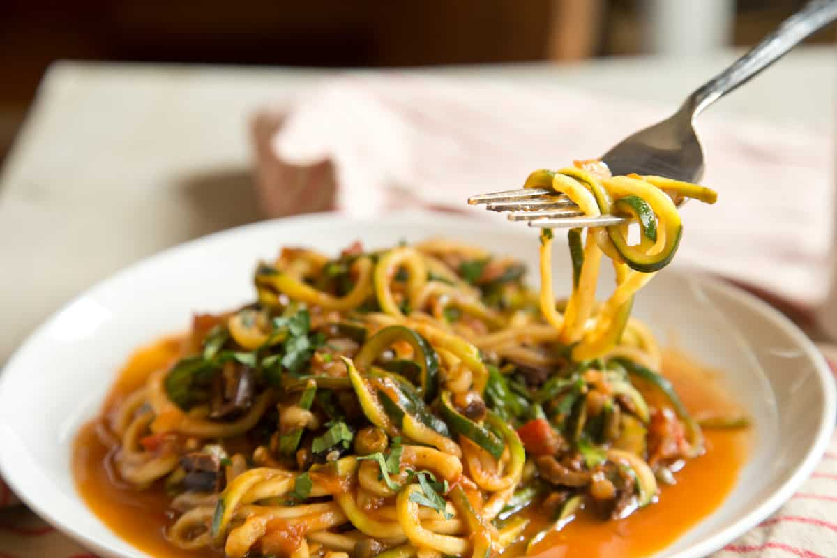 Vegan zucchini puttanesca made with spiralized zucchini noodles is a boldy flavored, surprisingly filling dish that won't weigh you down. #zoodles #zucchininoodles #vegan