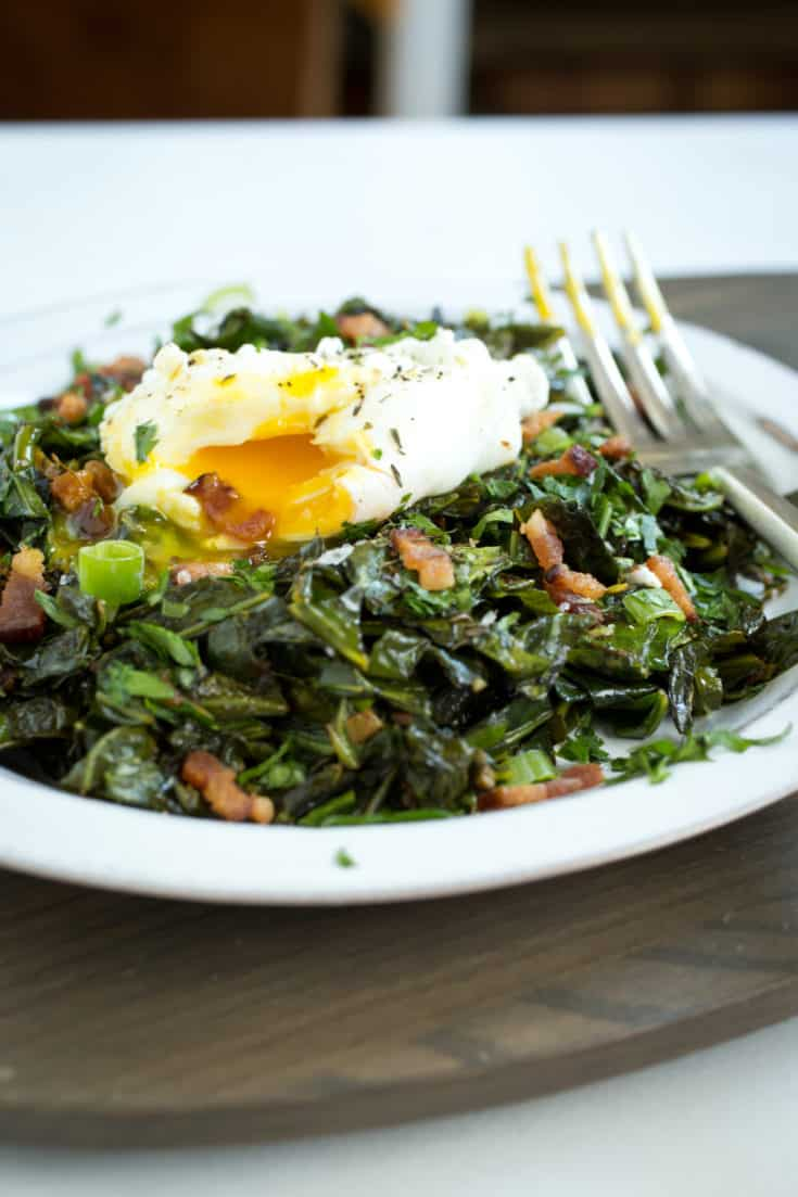 Collard greens are a mainstay of Southern soul food. This modern preparation of spiced collard greens pairs the sturdy vegetable with bacon and eggs. #collardgreens #southernfood #southernbrunch