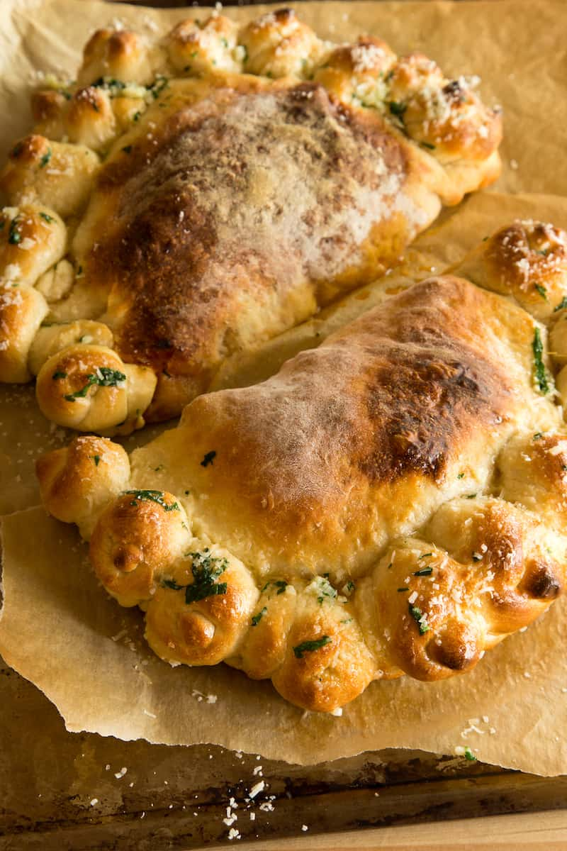 Garlic knot calzones take the idea of a garlic knot stuffed pizza crust and make it even better. Bake up 2 big calzones that feed a crowd!