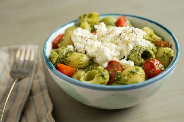 watercress pesto in pasta with ricotta and tomatoes