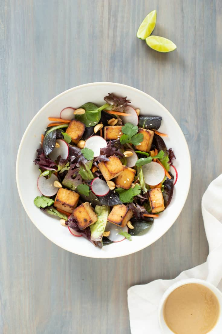 Tofu salad with lime tahini dressing is just one of the many mouthwatering ways you can make crispy baked tofu into a meal. #bakedtofu #tofusalad #tahinidressing