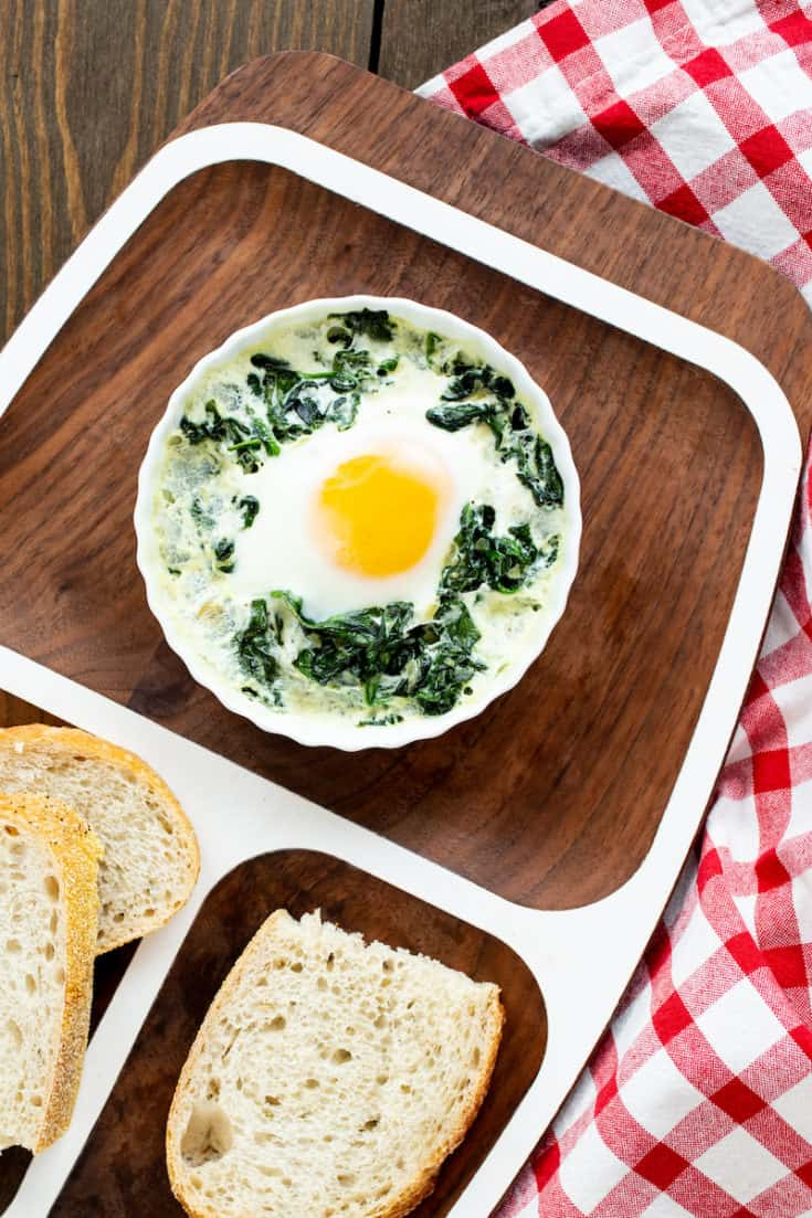 Baked eggs in ramekins with spinach and cream can be made as individual servings or as a beautifully presented meal for a brunch party. #bakedeggs #breakfast #brunch