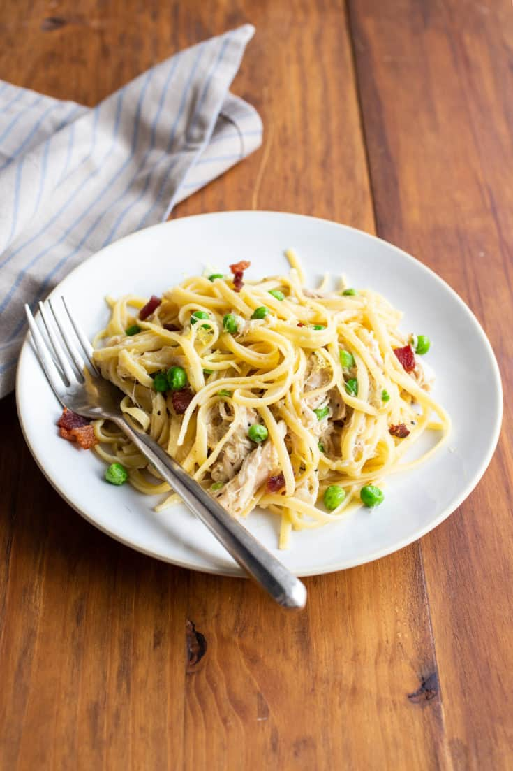 Instant Pot chicken pasta with peas and bacon requires a bit of hands-on attention, but you'll be rewarded with a bowl of tender pulled chicken and noodles. #instantpot #weeknightdinner #pasta #pulledchicken