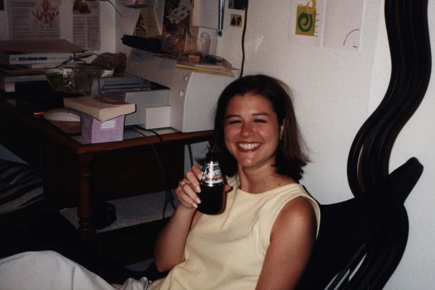 girl holding up a beer in a dorm room